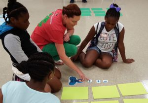 4-H Agent teaches robotics game to 3 young girls using pictures and cardstock.
